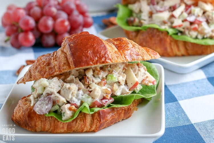 chicken salad sandwich with grapes in the background