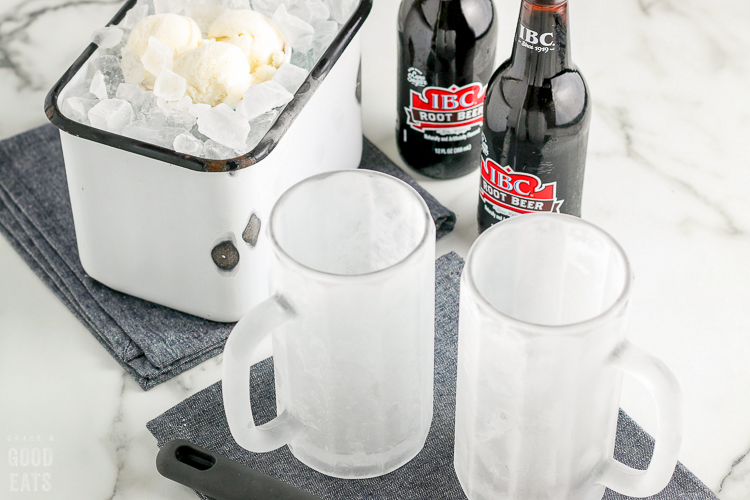 frosted mugs next to ice cream on ice and root beer bottles