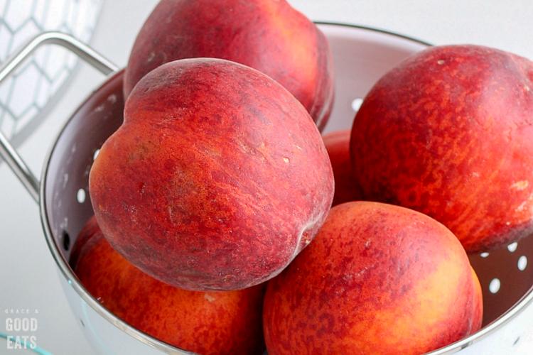 colander full of fresh peaches