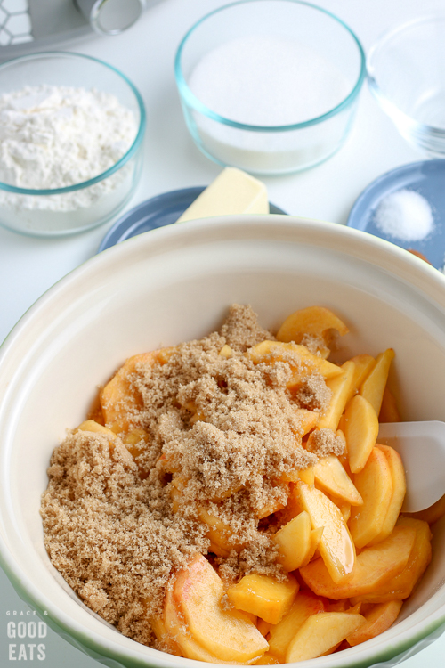 brown sugar and sliced peaches in a mixing bowl