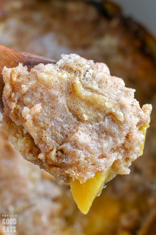 wooden spoon with a scoop of peach cobbler