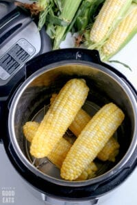 four cooked ears of corn in a pressure cooker