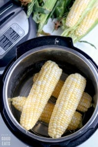 four uncooked ears of corn in a pressure cooker
