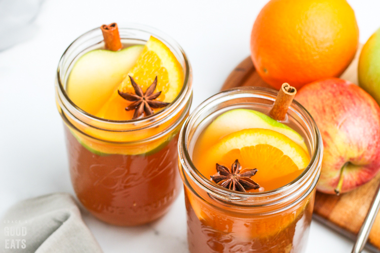 cider in a glass jar with orange slices and cinnamon sticks