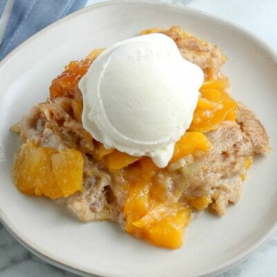 closeup of white plate with peach cobbler and vanilla ice cream