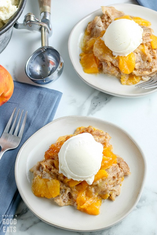 overhead shot of two plates with peach cobbler and vanilla ice cream