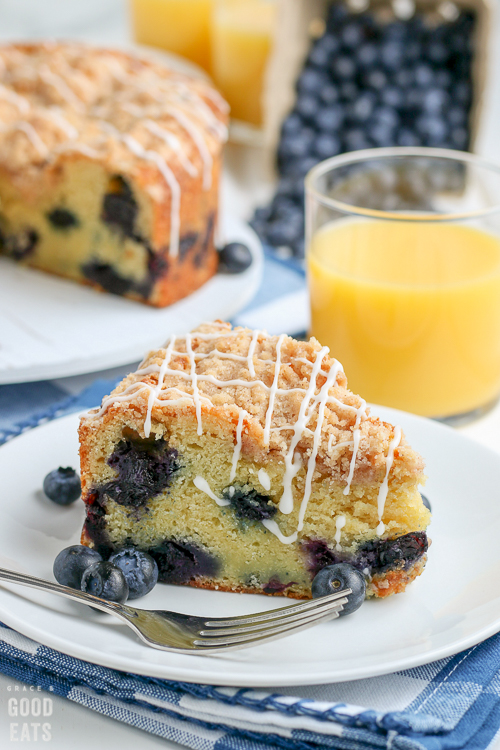 slice of blueberry coffee cake next to a fork and glass of orange juice