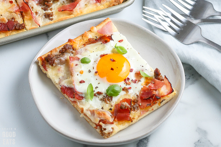 slice of breakfast pizza with a sunny side up egg