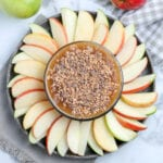 overhead view of a bowl of caramel apple dip with apples around it