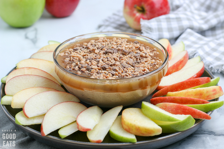 caramel apple dip surrounded by apple slices on a platter