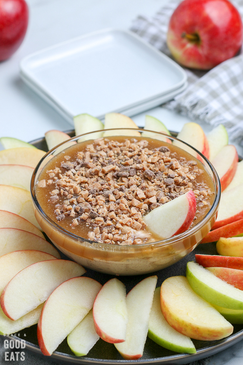 bowl of caramel sauce with apple slice in the caramel