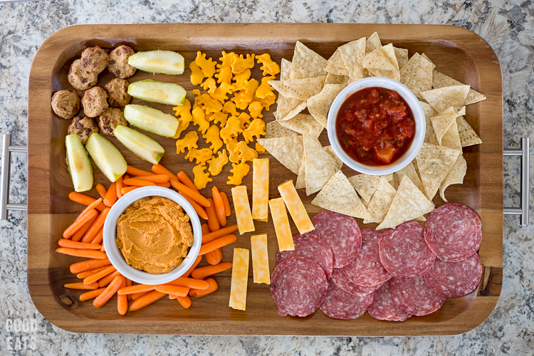 wooden tray with silver handles full of snacks like cheese sticks, salami, and crackers