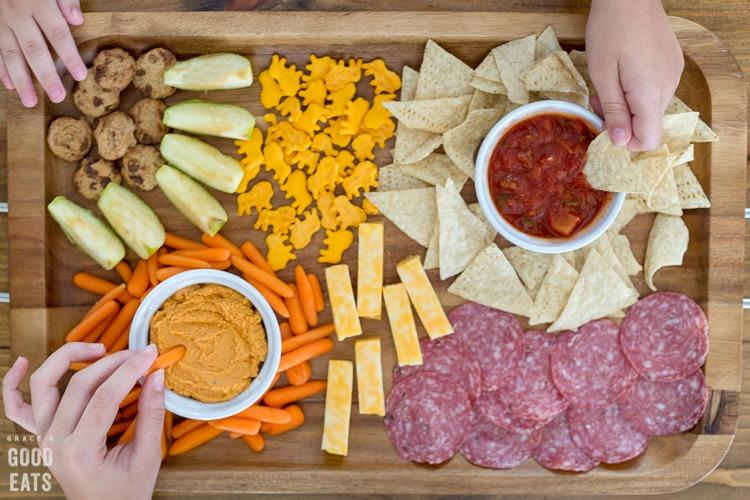 three kids hands reaching for snacks on a wooden snack board