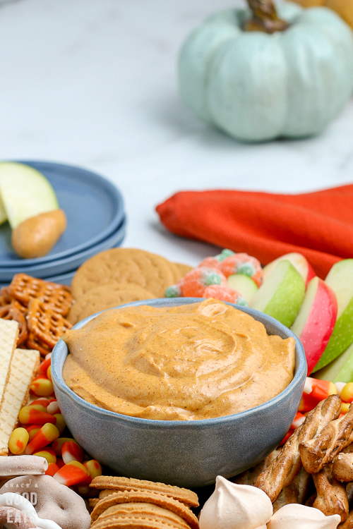 pumpkin dip in a blue bowl with pumpkins in the background