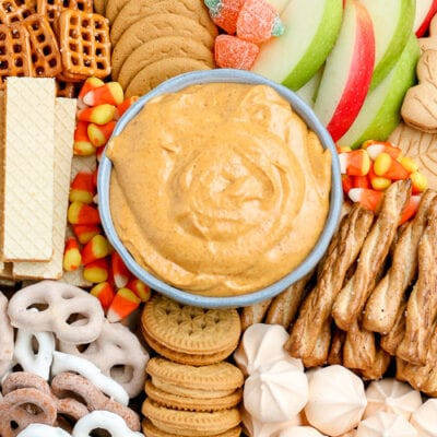 bowl of pumpkin dip surrounded by cookies and apple slices