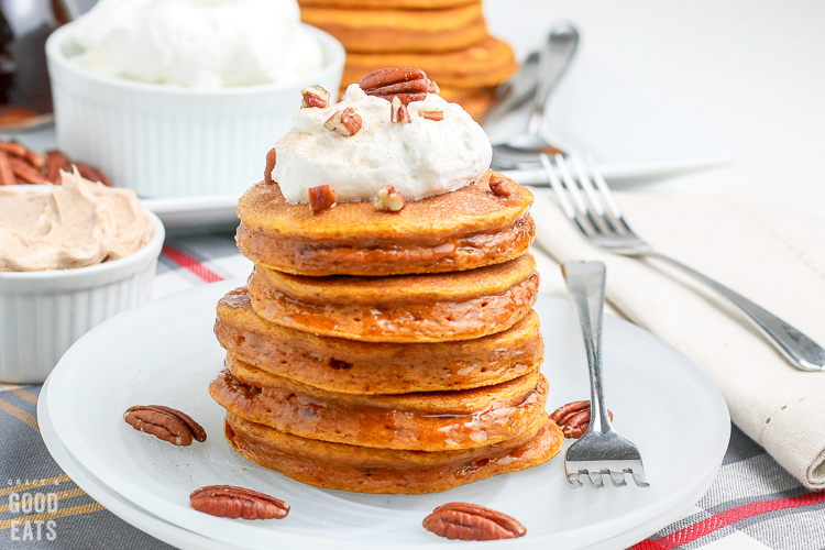 pumpkin pancakes on a white plate topped with whipped cream and pecans
