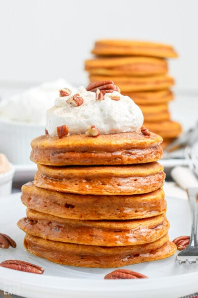 pumpkin pancakes stacked on a plate with more in the background