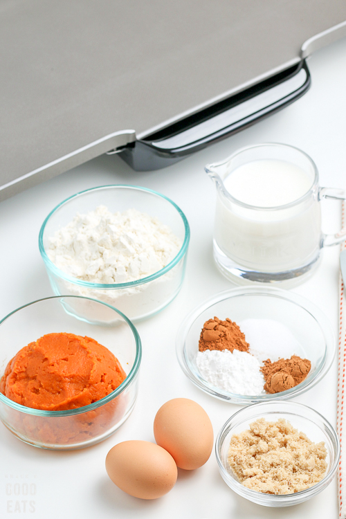 pumpkin pancake ingredients in small glass bowls next to a griddle