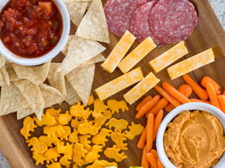brown wooden tray with chips and salsa, veggies and hummus, apple slices, salami, cheese, and crackers