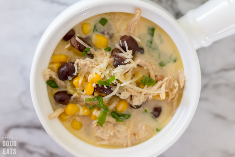 green chile chicken soup with corn and black beans in a white crock