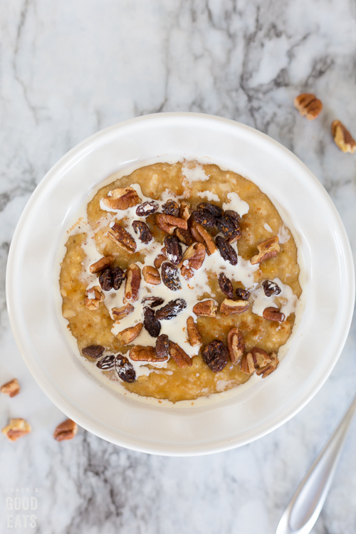 pumpkin oatmeal in a white bowl topped with cream, raisins, and pecans