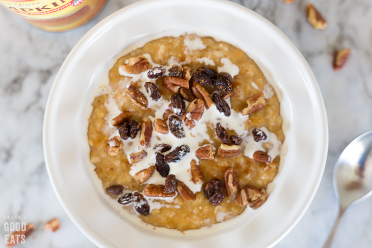 oatmeal in a white bowl topped with cream, raisins, and pecans