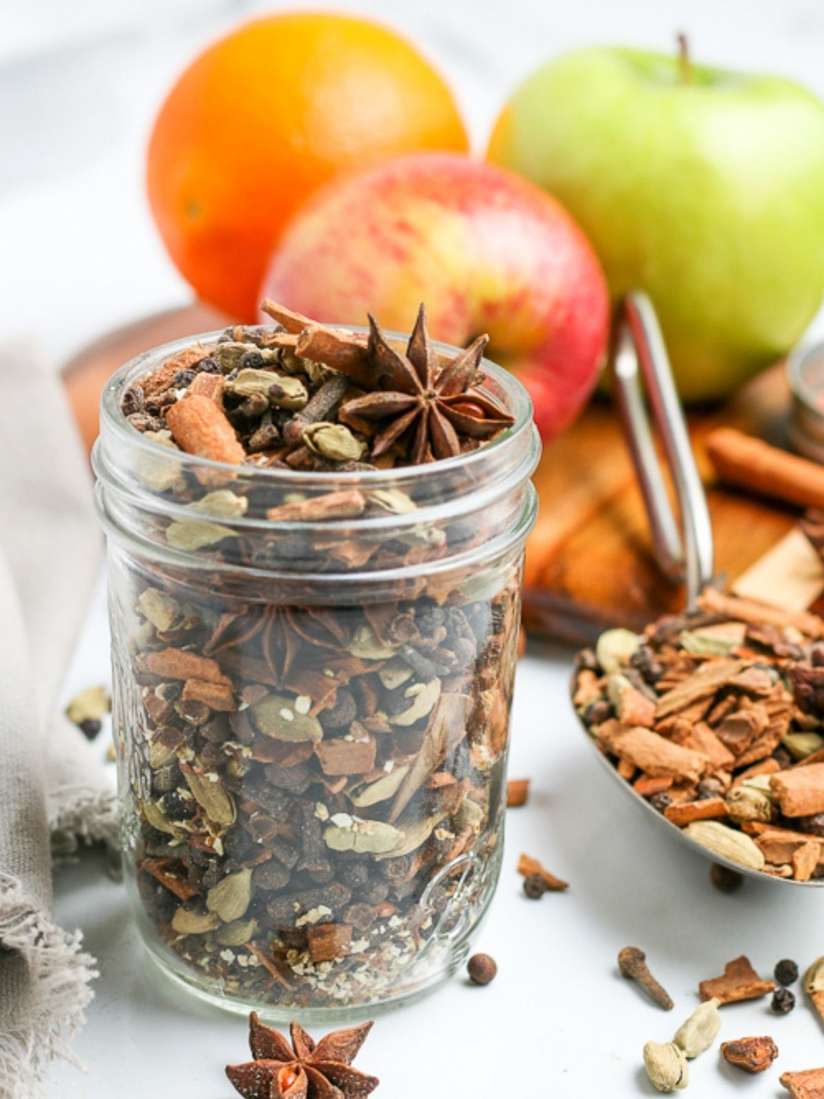 jar of mulling spices next to mulled cider and fruit