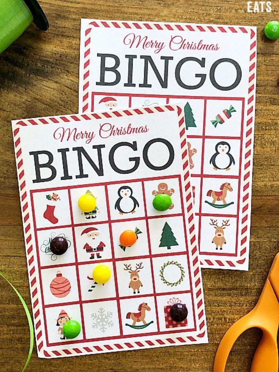 Christmas bingo cards next to ribbon and scissors