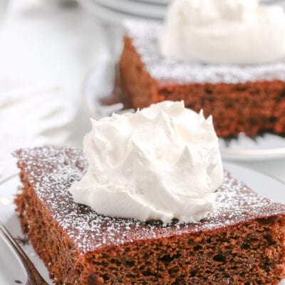 square slice of gingerbread cake on a white plate topped with whipped cream