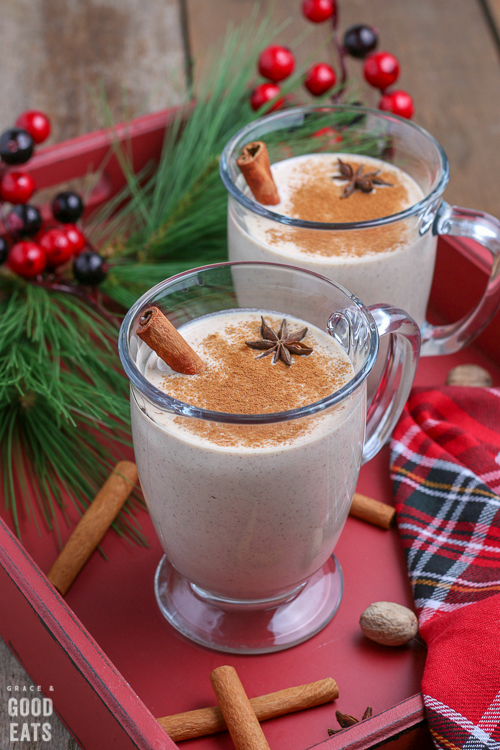 two glasses of eggnog on a red tray next to a Christmas napkin