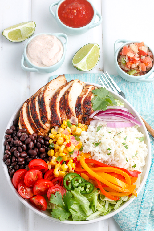 chicken burrito bowl in a white plate next to a blue linen