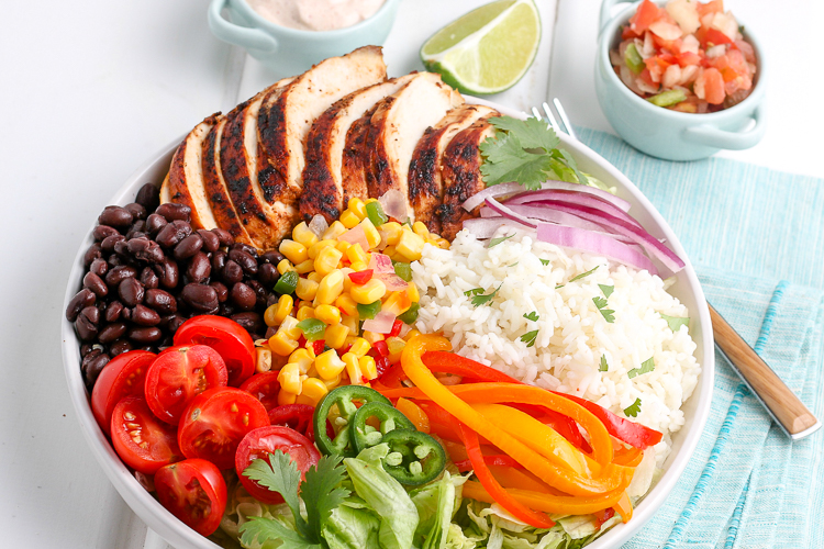 chicken burrito bowl ingredients arranged in a bowl