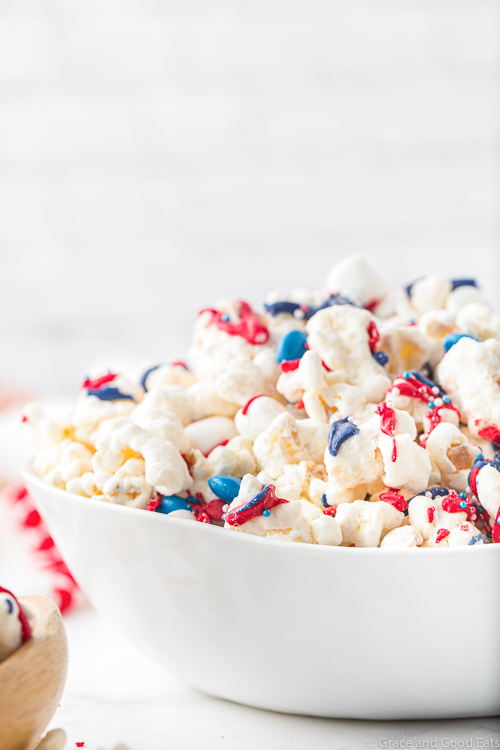 white bowl with patriotic popcorn with a white brick background