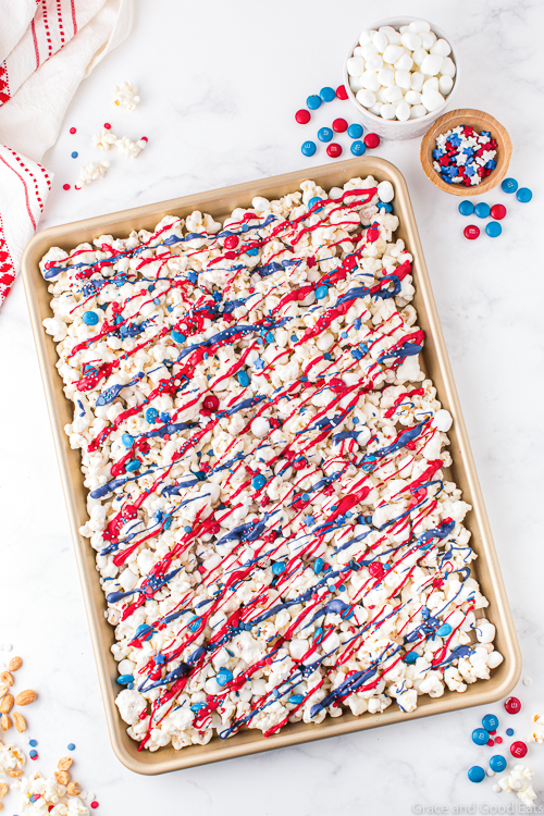 popcorn with red, white, and blue drizzle in a sheet pan